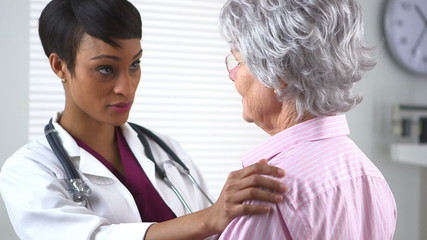 Nurse giving elderly woman a comforting hug