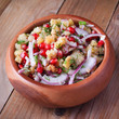 Potato salad with pomegranate seeds on wooden table