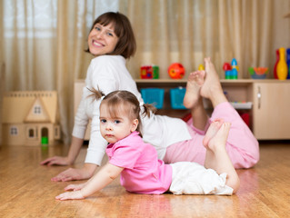 Mother and kid doing exercises laying on the floor in home inter
