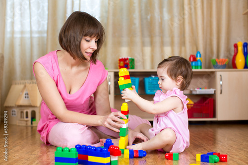Happy mother and kid play with toys at home interior