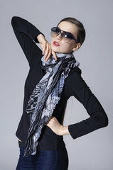 Model girl posing with scarf in studio on grey background