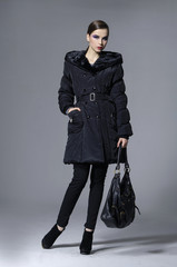 young elegant woman in coat with holding bag posing