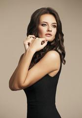 Girl in black dress simple. Portrait studio.