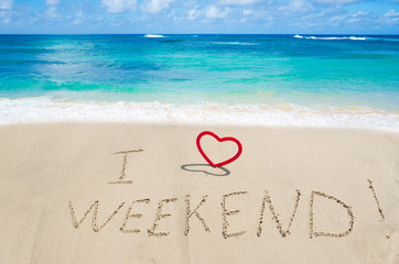 """Sign """"I love weekend"""" with hearts on the beach"""