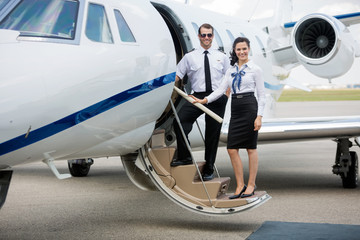 Airhostess And Pilot Standing On Private Jet's Ladder
