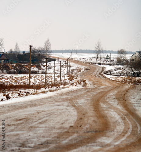 Winter rural landscape with a road in a village