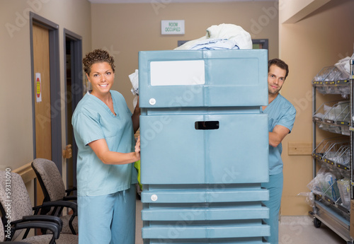 Nurses Pushing Trolley Filled With Linen In Hospital Hallway