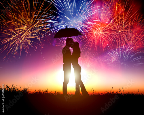 Couple kissing under umbrella with firework in the sky