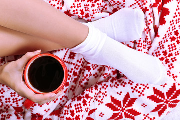 Composition with warm plaid,cup of hot drink and female legs,
