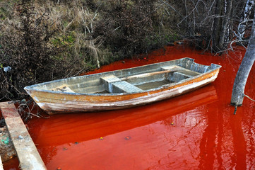 Abandoned boat in a contaminated red lake