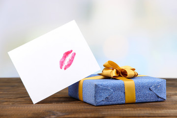 Gift with card for loved one on table on room background