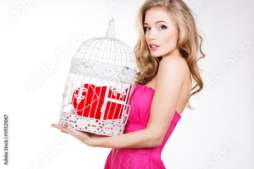 Pretty blonde girl holding white cage with red heart