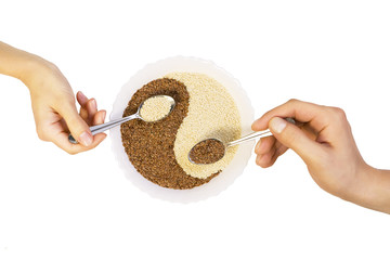 Eastern cuisine - man and woman hold spoons with sesame seeds in