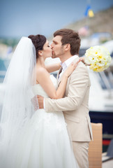 Bride and groom at wedding day kissing near yacht