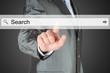 Businessman pushing virtual search bar on dark background .