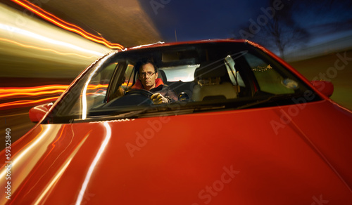 A man driving a red sports car at night.