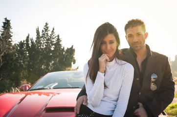 Young couple portrait with sport cabriolet car.