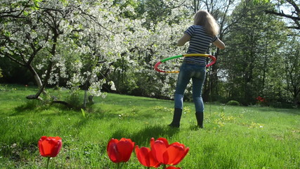 pretty woman turn hula hoop ring on waist in spring garden