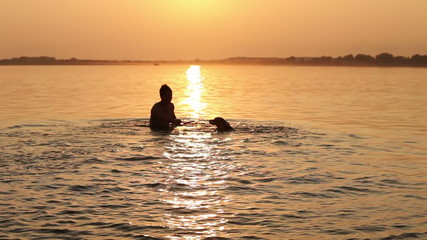 man with beagle puppy fooling around in ocean sunset waves