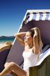 Beautiful woman on a wicker chair enjoying the sun on the beach