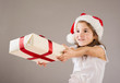 Small girl in santa hat with christmas gift