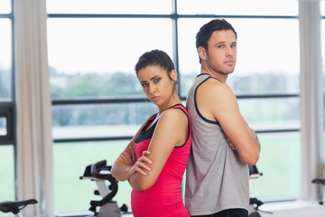 Serious young woman and man standing back to back in gym