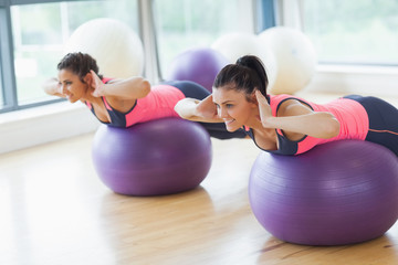 Two fit women exercising on fitness balls in gym
