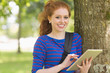 Smiling student leaning against a tree using her tablet