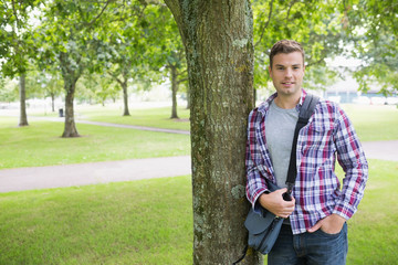 Smiling student leaning on tree looking at camera