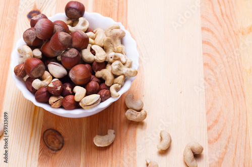 Plate with tasty nuts on the table