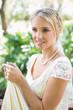 Smiling blonde bride holding her dress