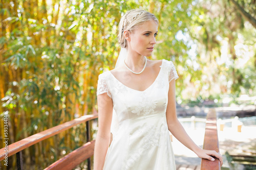 Smiling blonde bride in pearl necklace standing on a bridge © lightwavemedia
