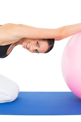 Side view portrait of a fit young exercising with fitness ball