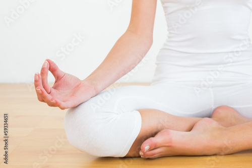 Close-up of woman in lotus pose at fitness studio