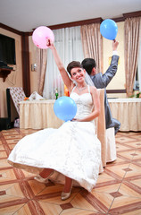 newly married couple holding up two different balloons
