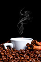 Cup of hot coffee with cinnamon on coffee beans