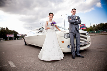 Young just married couple standing against long white limousine