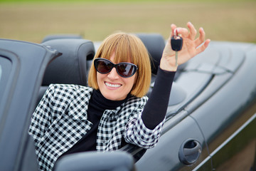 Middleaged woman with her new cabriolet