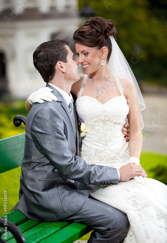 Beautiful bride sitting on grooms leg on bench and hugging him