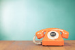 Retro orange telephone on table front mint green wall background - 59337621