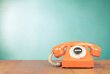 Retro orange telephone on table front mint green wall background