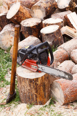 Powered professional chainsaw on pile of cut wood