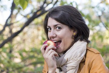 Young woman biting the red apple