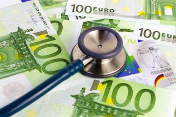 Stethoskop, Euro-Geldscheine und Krankenversichertenkarte