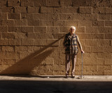 Old senior woman standing brick wall background