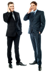 Two businessmen talking on cellphone