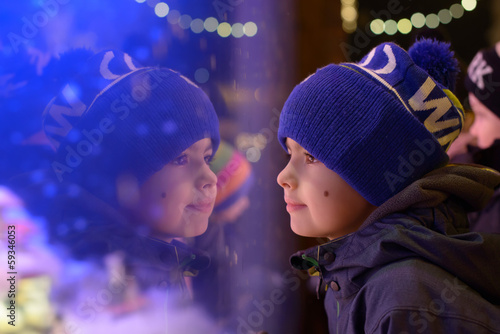 Boy looking into the shop window and dreaming