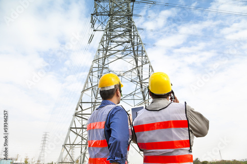 two workers wearing protective helmet works at electrical power
