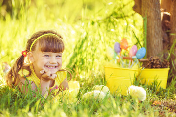 Happy little girl with a basket of small chickens sitting outdoo