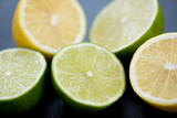 Ripe sliced limes and lemons, close-up, studio shot